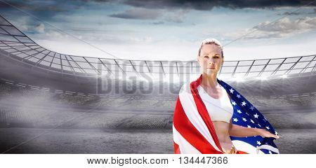 Portrait of sporty woman holding American flag against rugby stadium
