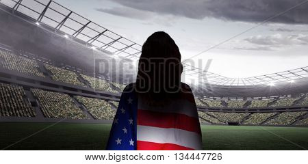 Rear view of sporty woman holding an American flag against rugby stadium