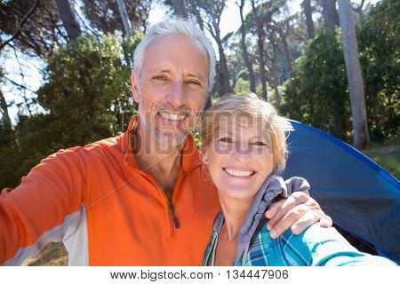 Mature couple taking a photo their camp site