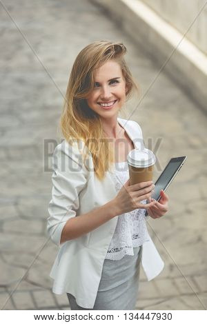 Young stylish woman drinking coffee to go in a city street. Image toned in vintage style.