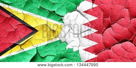 Guyana flag with Bahrain flag on a grunge cracked wall
