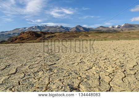 Scenic desert steppe landscape with mountains and the dry ground with cracks and sparse vegetation on a background of blue sky and clouds