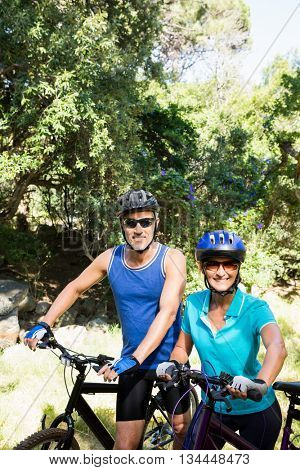 Mature couple with sunglasses posing with their bikes on the wood
