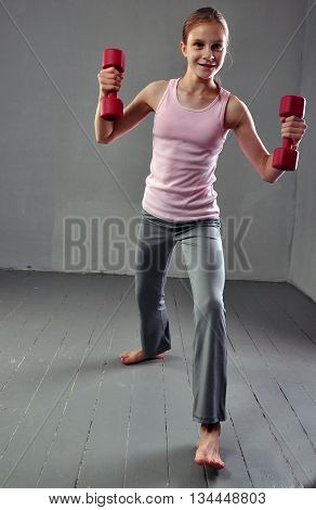 Teenage sportive girl is doing exercises with dumbbells to develop muscles isolated on grey background. Sport healthy lifestyle concept. Sporty childhood. Full length portrait of teenager child exercising with weights.