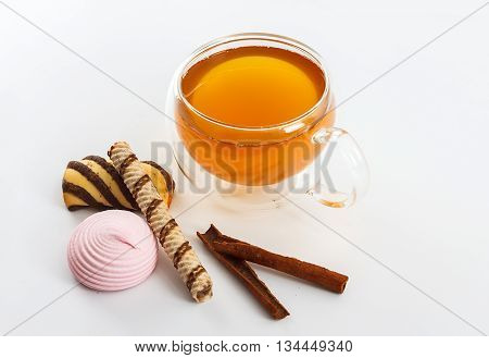 Double sided wall glass cup full of green tea with sweets biscuits and cinnamon next to it against white background close up horizontal view
