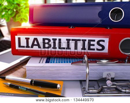 Red Office Folder with Inscription Liabilities on Office Desktop with Office Supplies and Modern Laptop. Liabilities Business Concept on Blurred Background. Liabilities - Toned Image. 3D.