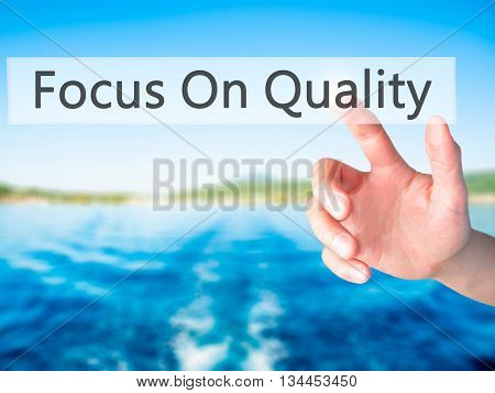 Focus On Quality - Hand Pressing A Button On Blurred Background Concept On Visual Screen.
