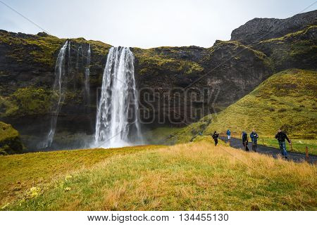 VIK ICELAND - OCTOBER 18 2015 : Tourists visit Seljalandsfoss Powerful waterfall and famous natural landscape in Southern Iceland.