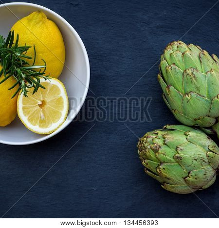 Organic fresh artichokes with lemon with copy space, grunge background. Selective focus, top view