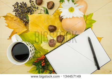 A Bouquet Of Yellow, Green Autumn Leaves With Cup Of Coffee And Blank Notebook With Pen