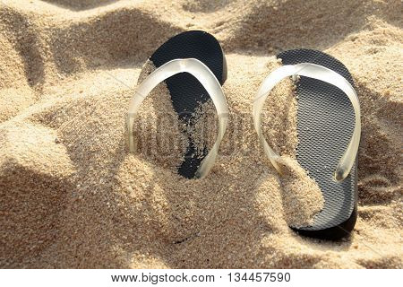 The Black flip flops on sand beach