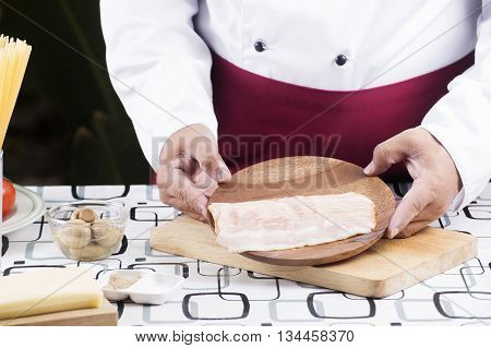 Chef present bacon for cooking spaghetti carbonala / cooking spaghetti concept