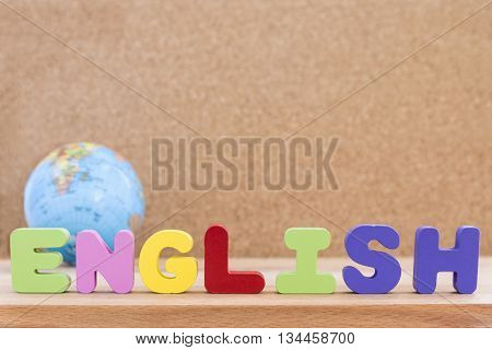 word english standing on the table with globe over wooden background with copy space education concept