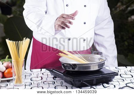 Chef putting spaghetti to boiled in the pan / cooking spaghetti concept