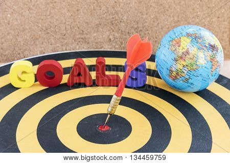 dart arrow hitting in target bullseye of center on dartboard with globe and word goals over wooden background with copy space business marketing success concept