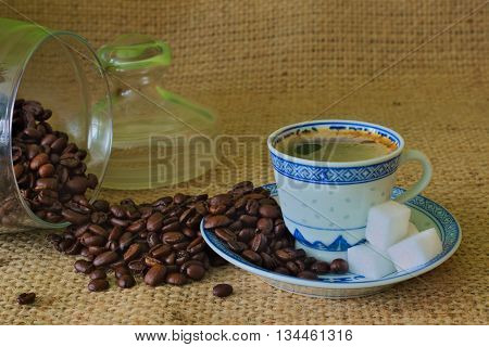 The photo shows a porcelain cup on a saucer filled to the full brown coffee. Cup is standing on a substrate made of raw, coarse fabric. A cup are scattered coffee beans and sugar cubes.