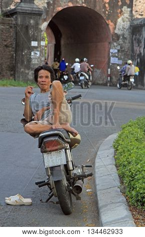 Man Is Sitting On A Scooter Outdoor In Hue, Vietnam