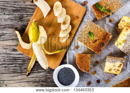 homemade banana cheesecake with poppy seeds and raisins on a parchment paper on an old wooden table with pieces of banana on a cutting board poppy seeds in a small bowl studio lights close-up