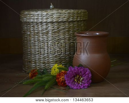clay jug, a wicker basket and wild flowers-rustic still life