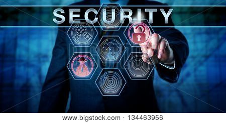Male corporate administrator is touching SECURITY on an interactive virtual control display. Business risk metaphor and information technology concept for physical security and computer security.