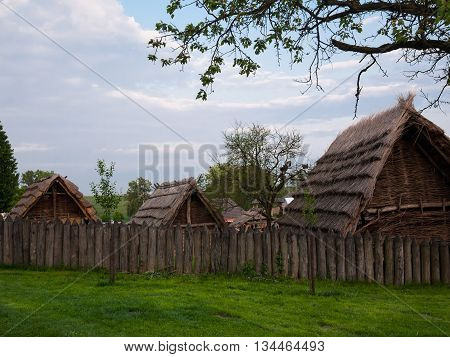 Roofs of Slavic shelters inside a wooden palisade