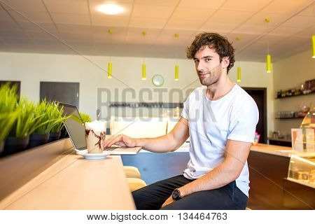 A Handsome young man sitting in a coffee shop using a laptop