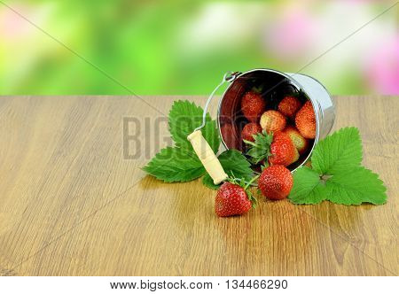Strawberry is scattered out of the bucket. strawberries with leaves in basket on wooden table on blurred background. Natural product from our own garden.