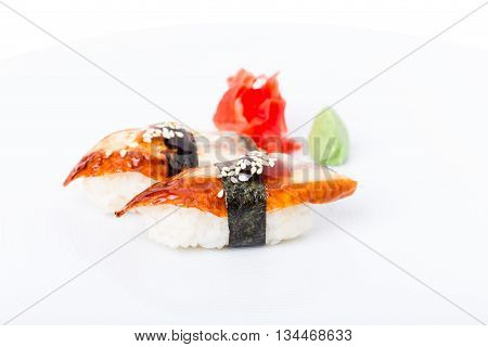 Nigiri sushi with smoked unagi and rolled with nori. Served with ginger and wasabi. Macro. Photo can be used as a whole background.