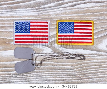 Small USA flag patches and military identification tags on rustic white boards. Fourth of July holiday concept for United States of America.
