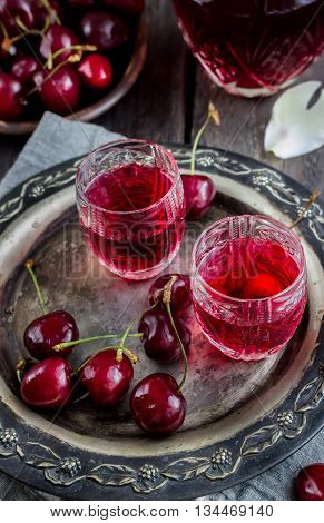 Cherry homemade liquor in a vintage glasses on metal tray and cherries. Wooden background selective focus.