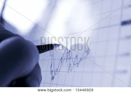 Businessman's hand showing diagram on financial report with pen