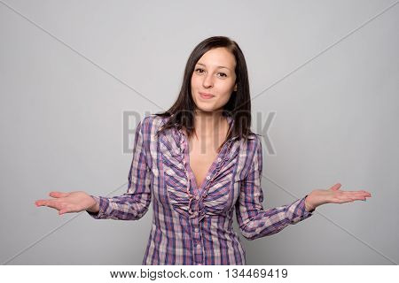 Portrait of doubtful woman isolated on gray background