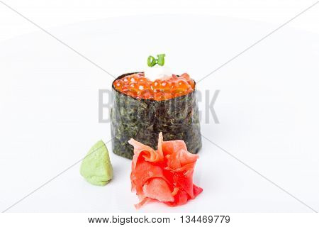 Gunkan sushi stuffed with red salmon caviar and mayonnaise. Served with heap of ginger and wasabi. Selective focus on heap of ginger. Macro. Can be used as a whole background.