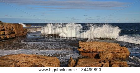 Coastal scene in Sydney. Rocks and splashing waves at Maroubra Beach.