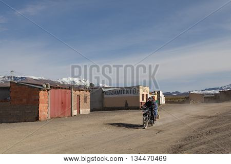 Sajama, Bolivia - October 27, 2015: Bolivian man and his wife riding a motocycle through the village.