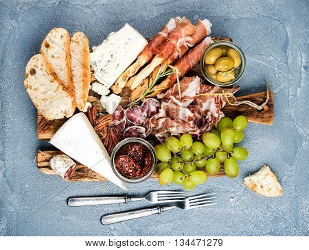 Cheese and meat appetizer selection. Prosciutto di Parma, salami, bread sticks, baguette slices, olives, sun-dried tomatoes, grapes and nuts on rustic wooden board over grey concrete textured backdrop, top view