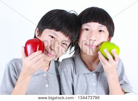 Portrait of two boys, twins holding red and green apples, isolated on white.