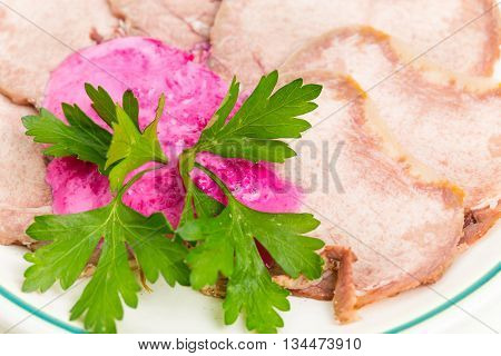 Baked veal tongue with horseradish cream and fresh parsley. Macro. Photo can be used as a whole background.