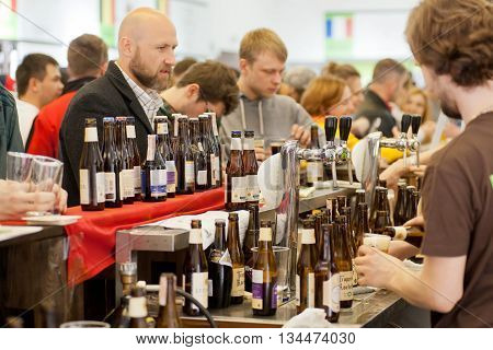 KYIV, UKRAINE - MAY 21, 2016: Man buying beer at the bar counter in crowd of people during Beermaster Day Festival on May 21, 2016. Kiev is the 8th most populous city in Europe.