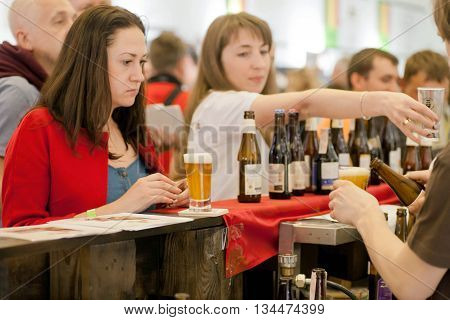 KYIV, UKRAINE - MAY 21, 2016: Sad woman buying beer at the bar counter in crowd of people during Beermaster Day Festival on May 21, 2016. Kiev is the 8th most populous city in Europe.