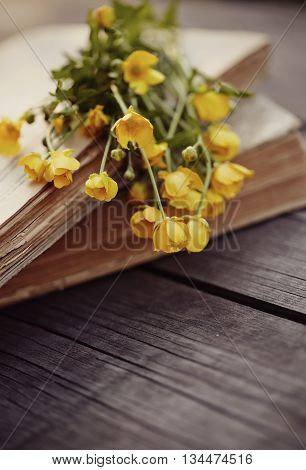Old books and bouquet of buttercups on a wooden table.