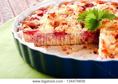 Horizontal photo of strawberry cake with one portion cut off. Green strawberry leaf placed on fruit pie. Pie in blue ovenproof dish on green towel and old brown wooden board.