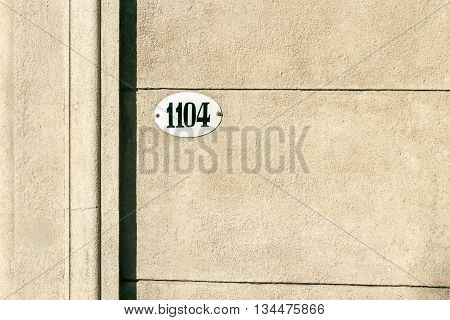 Enameled house number on baeige facade of concrete masonry