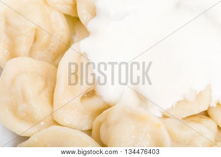Russian pork dumplings pelmeni with fresh sour cream. Macro. Photo can be used as a whole background.