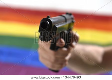 man holding close up gun with background gay parade flag representing sexual discrimination and intolerance and attack to human rights and sexual freedom
