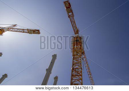Building crane against blue sky. Construction site. Low angle view. Construction concept