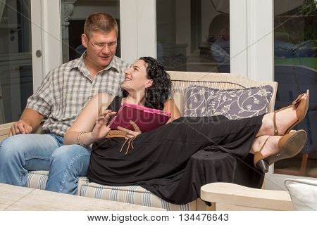 A couple sits on a bench with woman lying down with tablet in hand.