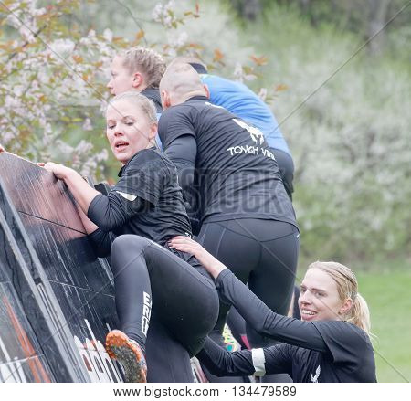 STOCKHOLM SWEDEN - MAY 14 2016: Smiling women climbing over a plank obstacle in the obstacle race Tough Viking Event in Sweden May 14 2016