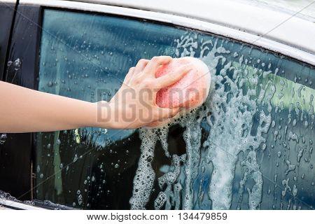 Male Hand Washing Car Window With Sponge
