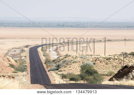 A tarmac road cuts through a salt pan known as Haakskeenpan